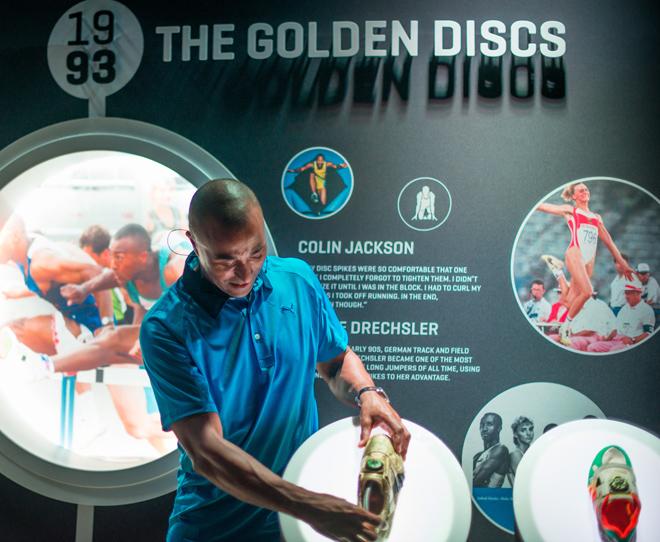 Колин Джексон рядом с моделью обуви, в которой он установил мировой рекорд