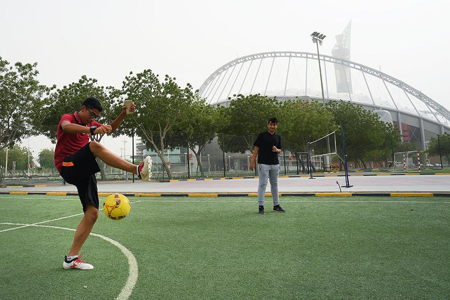 Подростки играют в футбол у стадиона «Халифа»