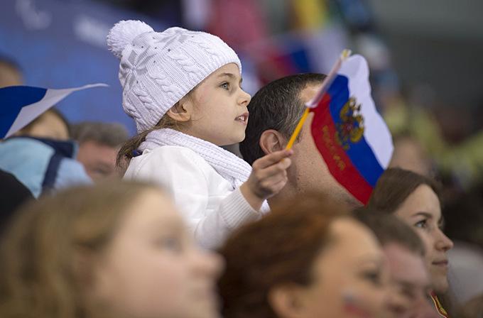 Юная болельщица наблюдает за событиями матча по следж-хоккею