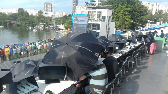 Журналисты прячутся под зонтиками на гребном канале