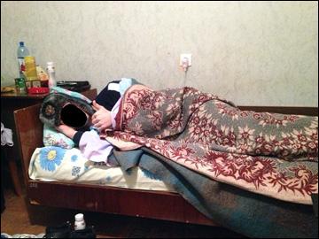 """Игроки """"Дизеля"""", спящие в одежде, шапке и кутающиеся в одеяла (лицо хоккеиста по понятным причинам скрыто)"""