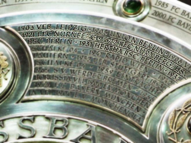 Посмотрите на трофей, вручаемый чемпиону бундеслиги: на нём выгравированы через дробь названия обоих клубов