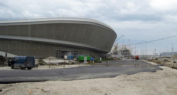 Асфальт в восьмом повороте на фоне конькобежного центра
