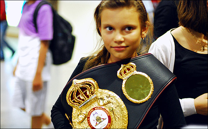 Дочь Александра Поветкина Арина позирует перед объективом фотокамер вместе с чемпионским титулом отца