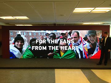При этом на экране появилась фотография болельщиков в шарфах, обнимающих Обафеми Мартинса