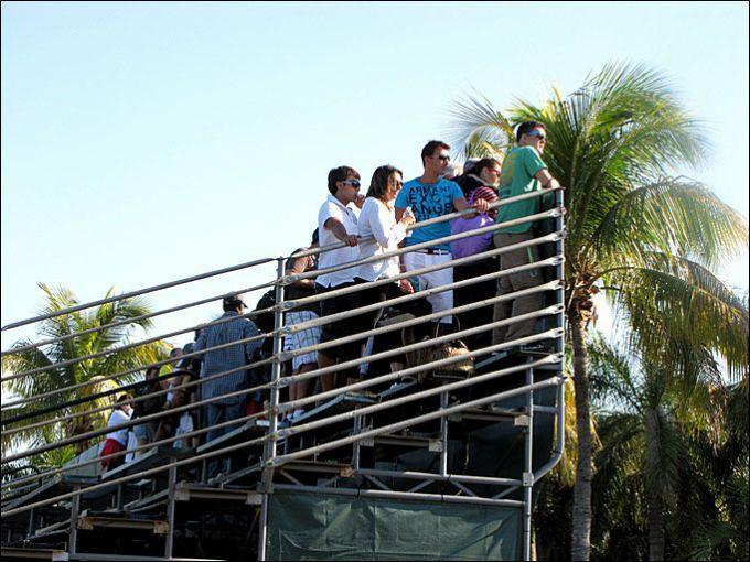 Люди на четвёртом корте смотрят парный матч с первого корта
