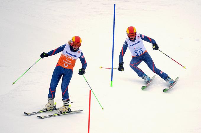 Гид Рэчел Ферье помогает англичанке Милли Найт преодолевать дистанцию в горнолыжном слаломе
