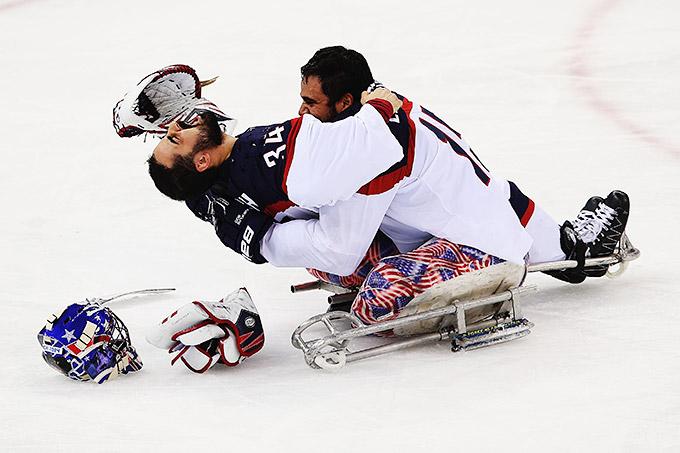 Американцы Стив Кэш и Никко Лендрос празднуют победу в финале следж-хоккейного турнира
