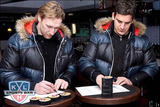 Алексей Ковалев и Бранко Радивоевич подписывают шайбы