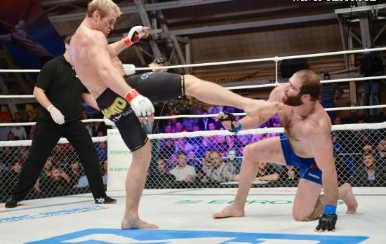 Запрещённый удар ногой Глухова в голову по стоящему на трёх точках опоры Газаеву.