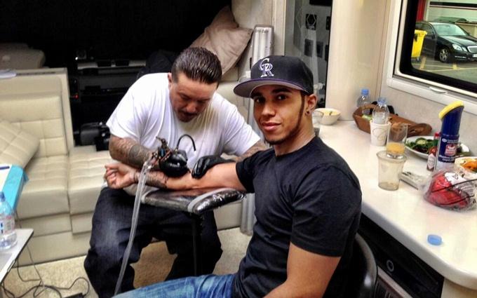 Льюис Хэмилтон в процессе обретения татуировки