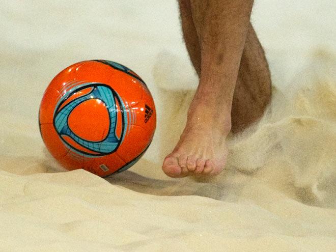 Нога, мяч и песок